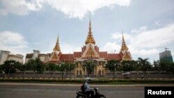 FILE: A man rides a motorcycle past the National Assembly in Phnom Penh August 26, 2014. Cambodia's opposition on Tuesday boosted its influence in a parliament long controlled by the ruling party, winning a deputy chairman post and assurances of greater legislative sway under a deal to end a year-long political impasse. The election of Kem Sokha as deputy house speaker is one of a slew of concessions by Prime Minister Hun Sen seldom seen during his three-decade grip on politics, reflecting the opposition's newfound power and growing public discontent with an authoritarian premier. REUTERS/Samrang Pring (CAMBODIA - Tags: POLITICS ELECTIONS)