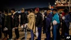 2020年1月15日,从利比亚沿海被敞开胸怀组织救起的一些孟加拉国男子在意大利麦锡纳港排队等待警察登记。(美联社)