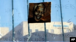 A print of Nelson Mandela and get-well messages hang outside of the Mediclinic Heart Hospital where former South African President Nelson Mandela is being treated in Pretoria, South Africa, June 24, 2013.