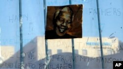 2013年6月24日在南非比勒陀利亚一家医院外面,悬挂支持和祝福曼德拉早日康复的图片,曼德拉目前就在这家医院治疗。