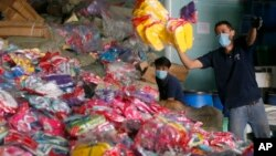 Workers unload counterfeit goods, mostly rubber slippers and sandals, for shredding at a customs-bonded warehouse at Cabuyao township, Laguna province southeast of Manila, Philippines, April 6, 2016.