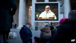 People watch Pope Francis on a giant screen at St. Peter's square as he celebrates his inaugural Mass with cardinals inside the Sistine Chapel, at the Vatican, March 14, 2013.