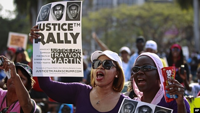 Female residents hold up images of black teenager Trayvon Martin and a packet of Skittles candy during a rally demanding justice for his killing in Miami, Florida April 1, 2012.
