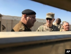 FILE - U.S. Army Lt. Gen. Stephen Townsend, center right, speaks with an Iraqi officer during a visit to an area north of Baghdad, Feb. 8, 2017.