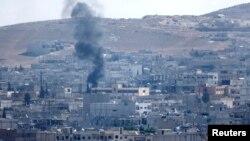 24일 접경 지역인 터키 수루크에서 바라본 시리아 코바니에서 연기가 피어오르고 있다.