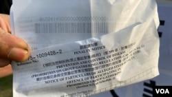 """懷疑被送中港人鄭子豪父親展示警方向他發出的防疫""""限聚令""""告票。(美國之音湯惠芸拍攝)"""