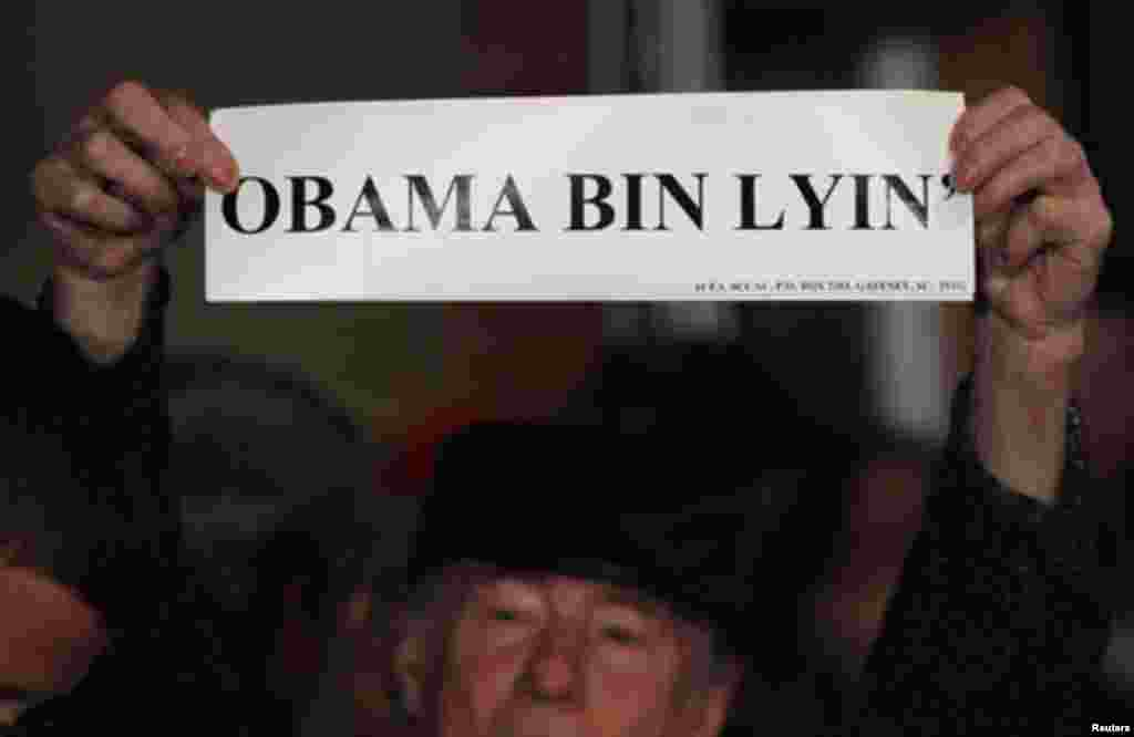 """A man holds a sign reading """"Obama Bin Lyin'"""" before a campaign rally with Republican presidential candidate and former Massachusetts Governor Mitt Romney in Columbia, South Carolina January 11, 2012."""
