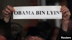 "Pendukung Mitt Romney membawa tulisan ""Obama Bin Lyin'"" sebelum kampanye capres partai Republik Mitt Romney (foto: dok). Tim kampanye Romney dan Obama saling serang dengan memasang iklan negatif atas lawan politiknya di TV."