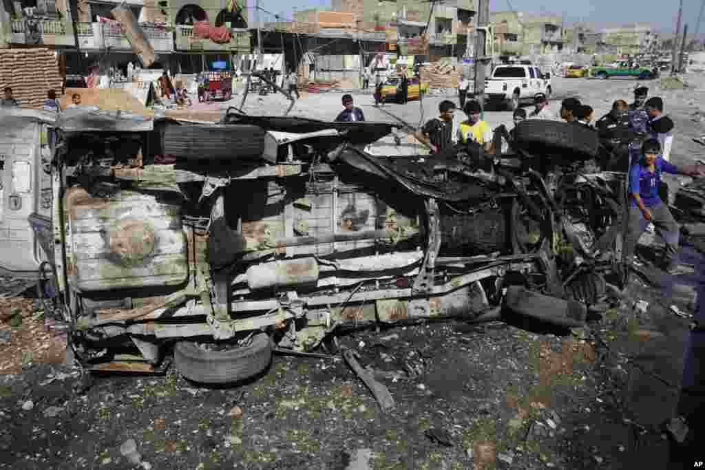 Iraqis inspect the aftermath of a car bomb attack, in the Shi'ite enclave of Sadr City, Baghdad, July 29, 2013.