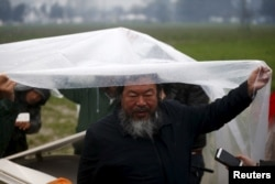 Chinese dissident artist Ai Weiwei speaks to reporters as he holds a rain cover to protect Syrian musician Nour Alkhzam from the rain, after her performance in a field near a makeshift camp on the Greek-Macedonian border, near the village of Idomeni, Gree