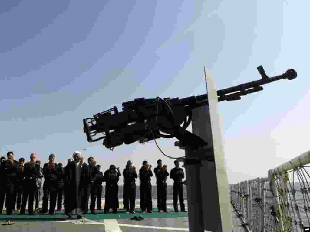 Military personnel pray as they stand behind a cleric on a naval ship during war games near the Strait of Hormuz on January 1, 2012.(Reuters)