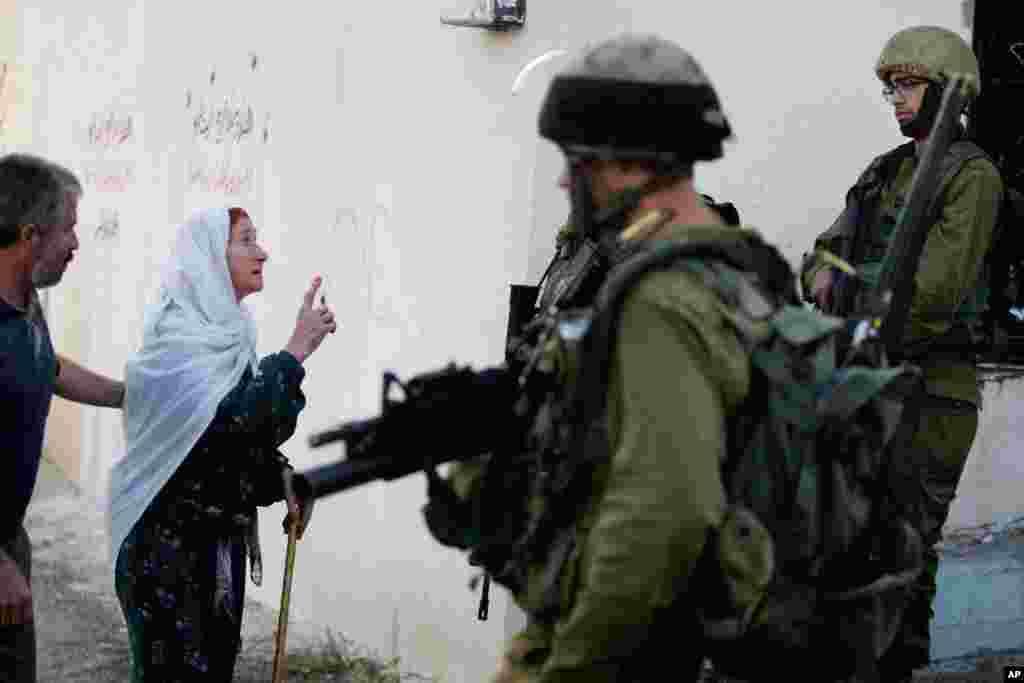 이스라엘 군 공습에 사망한 팔레스타인인 희생자의 친적이 요르단 서안지구의 한 마을에서 군인들에게 항의하고 있다. 이스라엘 군은 자신들에게 발포한 이 청년을 팔레스타인 무장군인으로 간주하고 사살했다고 밝혔다.