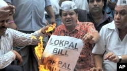 Anti-corruption activists burn symbolic copies of the Lokpal Bill (anti-corruption bill) during a protest to denounce the proposal in its current form in Mumbai on August 4, 2011.