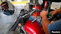 A man pumps gasoline at a service station in Caracas, Venezuela, Aug. 7, 2014.