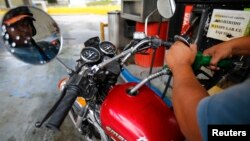 A man pumps gasoline at a service station in Caracas, Venezuela, Aug. 7, 2014.