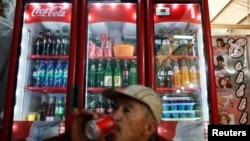 탄산음료가 가득찬 냉장고 앞에서 콜라를 마시고 있는 멕시코시티 근로자. (자료사진)
