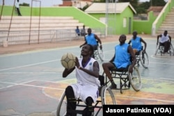 A wheelchair basketball player puts his artificial leg back on after a game at a basketball court in Juba, South Sudan, May 31, 2016.
