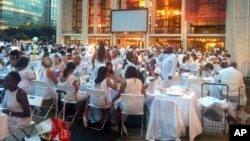 FILE - Guests wearing white clothing sit down to a pop-up dinner at New York's Lincoln Center, Tuesday, Aug. 22, 2017. The event, known as Diner en Blanc, French for Dinner in White, is an annual foodie tradition and began in Paris 29 years ago. (AP Photo)