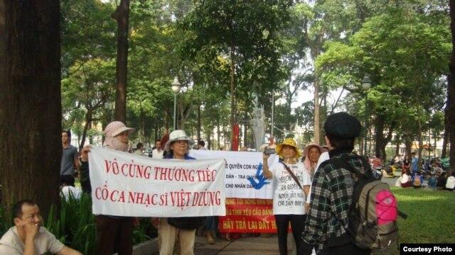 Người biểu tình mang băng rôn với hàng chữ 'Vô cùng thương tiếc cố nhạc sĩ Việt Dzũng'.