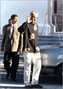 Nelson Mandela waves to supporters shortly before being inaugurated as South Africa's first democratic president … He's wearing his very first 'Madiba shirt,' given to him by Cape Town fashion designer Desre Buirski