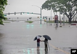 In this Aug. 23, 2018 file photo, people stand near flood waters from Hurricane Lane in Hilo, Hawaii. Some of Hawaii's most iconic beaches could soon be underwater. (Hollyn Johnson/Hawaii Tribune-Herald via AP, File)