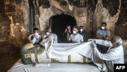 Egypt's Antiquities Minister Khaled al-Enany, right, and Mostafa Waziri, second right behind, the secretary-general of the Supreme Council of Antiquities, inspect an intact sarcophagus during its opening at Al-Assasif necropolis near Luxor, Egypt, Nov. 24, 2018.