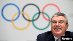 FILE - The Olympic rings are seen behind IOC President Thomas Bach at a news conference in Monaco, Dec. 6, 2014.