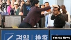 지난 1일 중동발 여객기를 타고 인천공항에 도착한 외국인이 메르스 검역 절차 중 정밀 체온측정을 받고 있다. (자료사진)