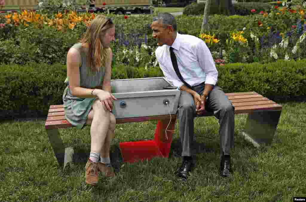 "U.S. President Barack Obama speaks with eco-friendly urban furniture designer Sandra Richter while hosting the first-ever White House ""Maker Faire"" in Washington, D.C., June 18, 2014. The solar-powered bench allows people to charge their phones while resting."