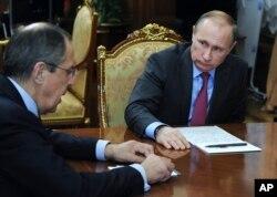ປະທານາທິບໍດີ ຣັດເຊຍ ທ່ານ Vladimir Putin ຂວາ ຟັງລາຍງານຈາກ ລັດຖະມົນຕີຕ່າງປະເທດ ຣັດເຊຍ ທ່ານ Sergey Lavrov.