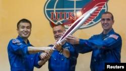 Para awak Stasiun Antariksa Internasional (ISS), dari kiri ke kanan, astronot Jepang Koichi Wakata, kosmonot Rusia Mikhail Tyurin dan astronot Amerika Rick Mastracchio, memegang obor Olimpiade Musim Dingin Sochi 2014 (6/11). (Reuters/Shamil Zhumatov)