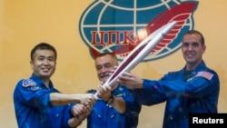 日俄美三名宇航员在拜科努尔航天基地升空前与奥运火炬合影。