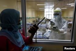 Nakes berbicara melalui walkie-talkie di ruang isolasi untuk pasien virus corona (Covid-19) di Rumah Sakit Persahabatan, Jakarta, 13 Mei 2020. (Foto: Reuters)