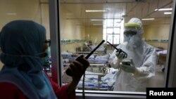 Pekerja kesehatan berbicara melalui walkie-talki di ruang isolasi untuk pasien virus corona (Covid-19) di Rumah Sakit Persahabatan, Jakarta, 13 Mei 2020. (Foto: Reuters)