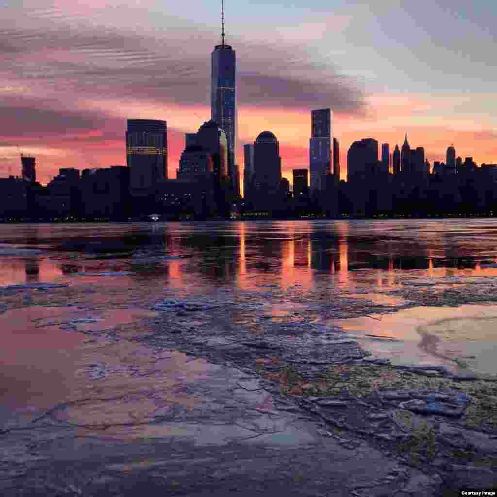The sun rises over lower Manhattan, reflected in the icy waters of the Hudson River (Photo taken by Daniel Leavey of Jersey City in New Jersey on Feb. 21, 2015)