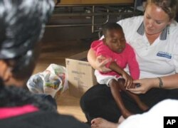 Occupational therapist Shannon Morgan holds one of her young patients while a relative looks on