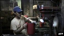 Un hombre trabaja en una fábrica de cubos. Hoteles, restaurantes, bares, pequeñas fábricas, tiendas e incluso vendedores de tortillas han bajado sus ventas, tras crisis política. Foto de archivo.
