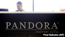 An employee works in the lobby of Pandora headquarters in Oakland, Calif., Tuesday, June 14, 2011