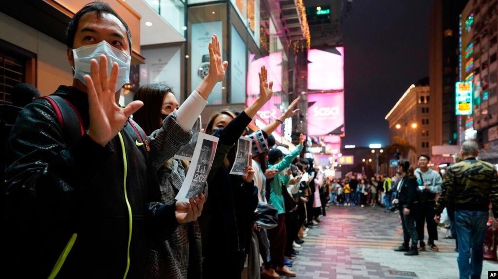 """香港抗议者在新年除夕夜组成人链,伸出手掌表示""""五项诉求,缺一不可""""。(2019年12月31日)"""