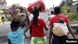 Une femme porte son enfant au dos et d'autres, leurs affaires sur une route de Bujumbura, Burundi, le 29 avril 2015.