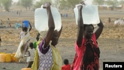 FILE - Internally displaced women carry water from a borehole at a camp near Kodok, in the north-eastern South Sudanese state of Western Nile, April 17, 2017.