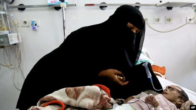 In this Tuesday, March 22, 2016 photo, Udai Faisal, who is suffering acute malnutrition is fed by his mother Intissar Hezzam at al-Sabeen Hospital in Sana'a, Yemen.  Hunger has been the most horrific consequence of Yemen's conflict and has spiraled since Saudi Arabia and its allies, backed by the U.S., launched a campaign of airstrikes and a naval blockade a year ago.