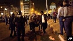 12月5日埃及穆尔西总统支持者和反对者在开罗总统府外发生冲突,反对者正撤下受伤的同伴