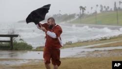 Seorang pria kesulitan menggunakan payungnya saat angin kencang dan hujan menjelang datangnya badai Harvey di kota Corpus Christi, Texas, Jumat (25/9).