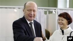 Peredana Menteri Lithuania dan pimpinan partai Serikat Tanah Andrius Kubilius dan istrinya, Rasa memasukkan surat suaranya di TPS Vilnius, Lithuania (14/10). Partai Kubilius hanya mendapatkan 13 persen suara dalam Pemilu Parlemen Luthuania.