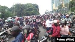 Pengendara sepeda motor yang berboncengan terpaksa harus balik arah dan tidak diperbolehkan masuk Surabaya pada hari pertama penerapan PSBB. (foto: VOA/ Petrus Riski)