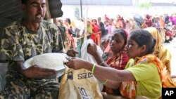 ** FILE ** A border guard sells rice at a government subsidized outlet at Nawabganj in Dhaka, Bangladesh, Friday, April 11, 2008. The price of food has skyrocketed around the world, leading to riots in some countries and fears of starvation in others, and