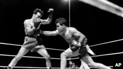 FILE - Jake LaMotta, right, is seen fighting Marcel Cerdan at Briggs Stadium, in Detroit, Michigan, June 16, 1949.