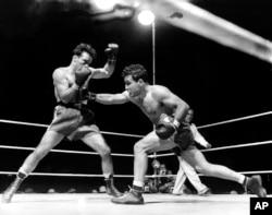 FILE - Jake LaMotta, right, is seen fighting Marcel Cerdan at Briggs Stadium, in Detroit, Michigan, June 16, 1949.