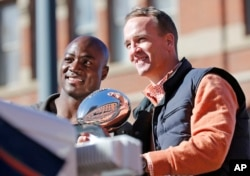 Denver Broncos quarterback Peyton Manning and defensive end DeMarcus Ware hold the Lombardi Trophy during a parade for the NFL football Super Bowl champions in Denver, Feb. 9, 2016.